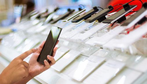 Person testing a smartphone at a retail store