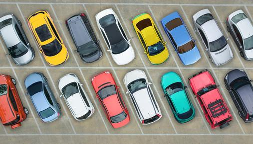 Overhead view of a row of cars parked in a parking lot