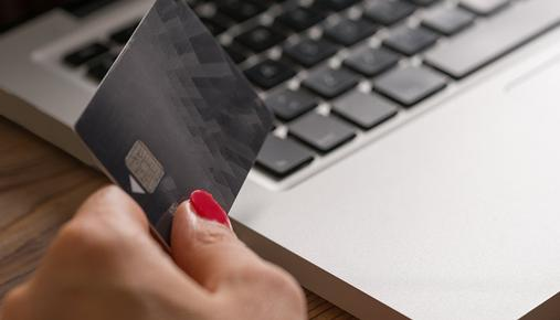 Woman's hand holding a credit card in front of a laptop