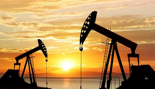 Oil wells in front of lake at sunset