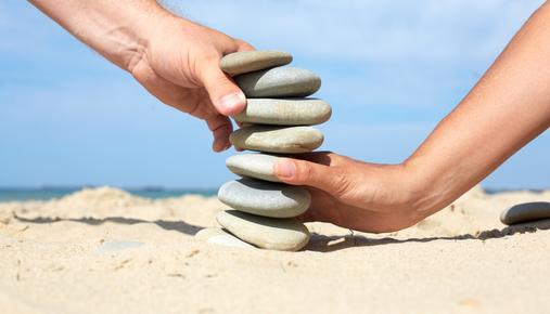 Financial Planning Symbolism as Two People Build Tower Out of Stones