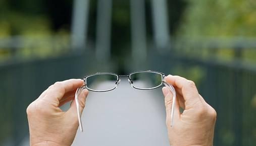 Person holding up a pair of glasses on a bridge